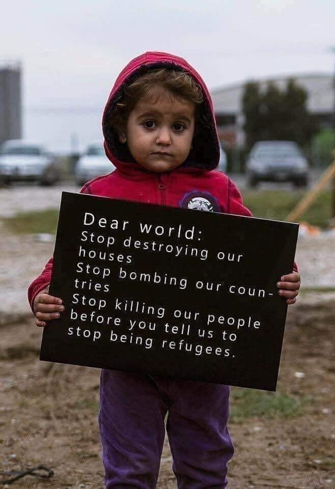 Sign held by small child says 'Dear world: Stop destroying our houses, stop bombing our countries, stop killing our people, before you tell us to stop being refugees.'
